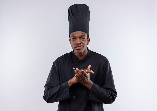 Young confident afro-american cook in chef uniform pretends to clap his hands isolated on white background with copy space