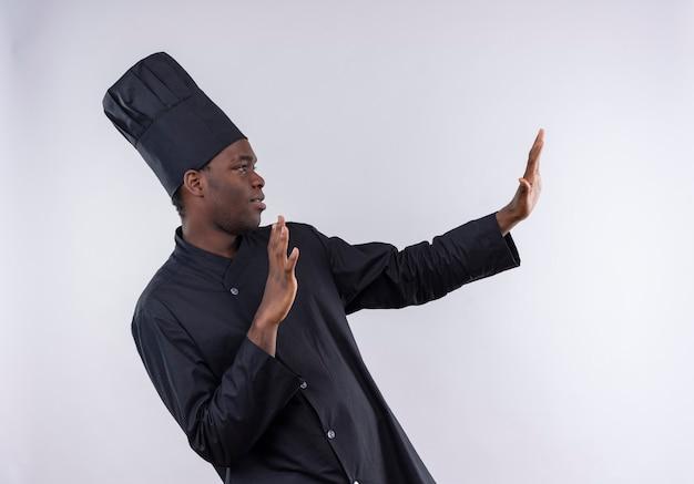 Giovane cuoco afroamericano fiducioso in uniforme da chef finge di difendere con le mani su bianco con lo spazio della copia