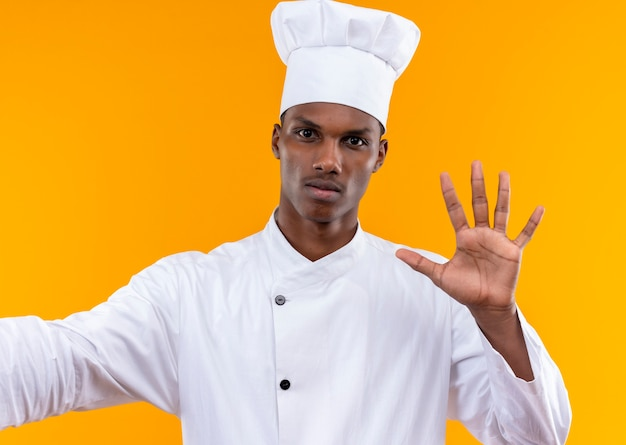 Young confident afro-american cook in chef uniform shows open hand isolated on orange background with copy space