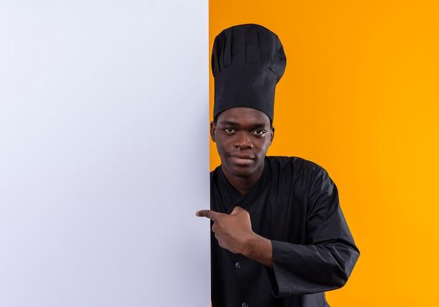 Il giovane cuoco afroamericano fiducioso in uniforme da chef sta dietro e indica il muro bianco isolato sullo spazio arancione con lo spazio della copia