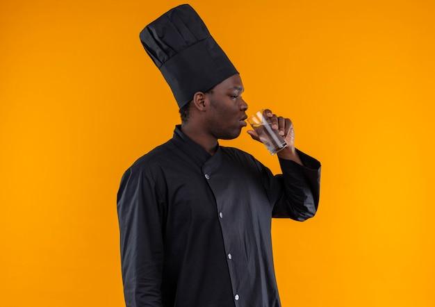 Giovane cuoco afroamericano fiducioso in uniforme da chef si leva in piedi lateralmente e beve un bicchiere d'acqua isolato su priorità bassa arancione con lo spazio della copia