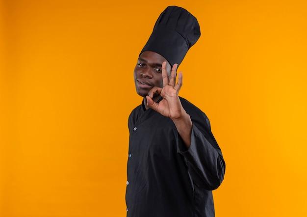 Giovane cuoco afroamericano fiducioso in uniforme da chef si leva in piedi lateralmente e gesti il segno giusto della mano sull'arancio con lo spazio della copia