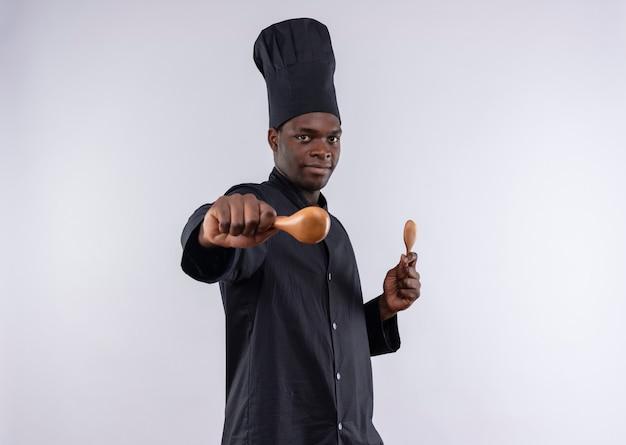 Il giovane cuoco afroamericano fiducioso in uniforme da chef si leva in piedi lateralmente e tiene i cucchiai di legno su bianco con lo spazio della copia
