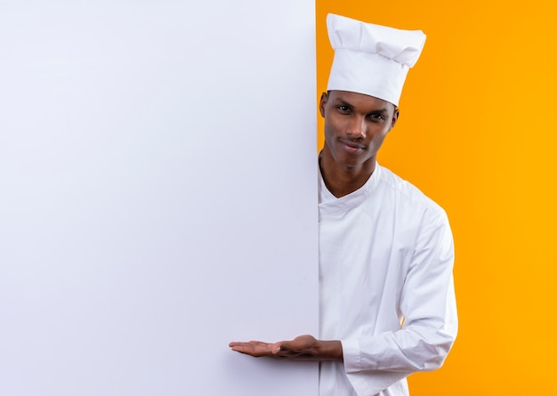 Young confident afro-american cook in chef uniform stands behind white wall and holds hand straight isolated on orange background with copy space