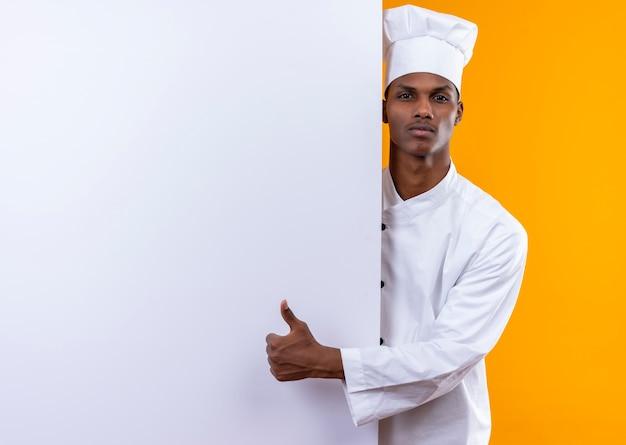Il giovane cuoco afroamericano fiducioso in uniforme dello chef sta dietro il muro bianco e il pollice in alto isolato su sfondo arancione con spazio di copia