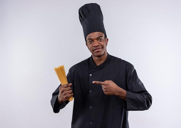 シェフの制服を着た若い自信を持ってアフリカ系アメリカ人の料理人は、コピースペースで白い背景に分離されたスパゲッティの束を保持し、ポイントします