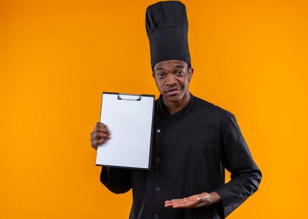 シェフの制服を着た若い自信を持ってアフリカ系アメリカ人の料理人はクリップボードを保持し、コピースペースでオレンジ色の背景にまっすぐに分離された手を保持します