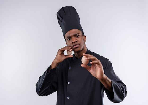 シェフの制服を着た若い自信を持ってアフリカ系アメリカ人の料理人は卵を保持し、コピースペースで白い背景に孤立して防御するふりをします