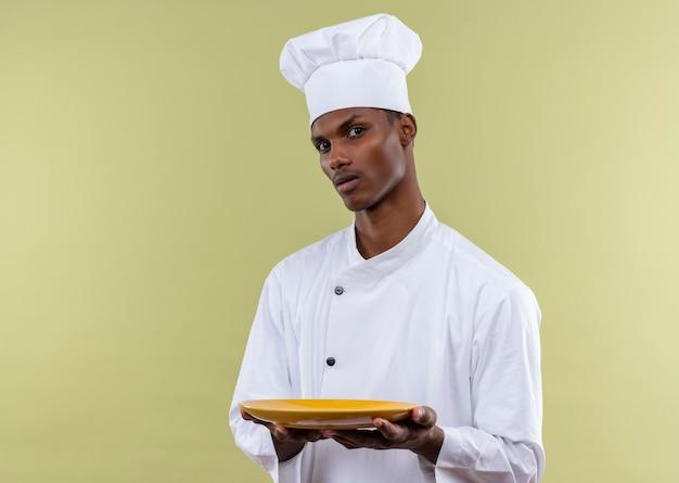 シェフの制服を着た若い自信を持ってアフリカ系アメリカ人の料理人は、コピースペースで緑の背景に分離された両手で空のプレートを保持します