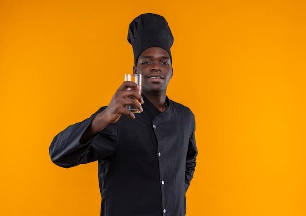 シェフの制服を着た若い自信のあるアフリカ系アメリカ人の料理人は、コピースペースでオレンジ色の水を保持します