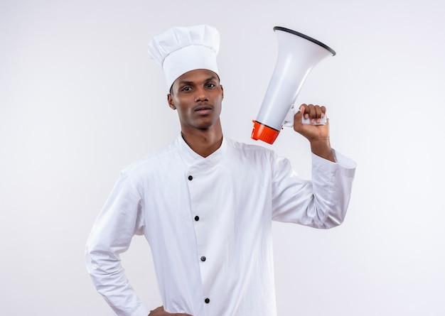 シェフの制服を着た若い自信を持ってアフリカ系アメリカ人の料理人は、スピーカーを保持し、コピースペースで白い背景で隔離の腰に手を置きます