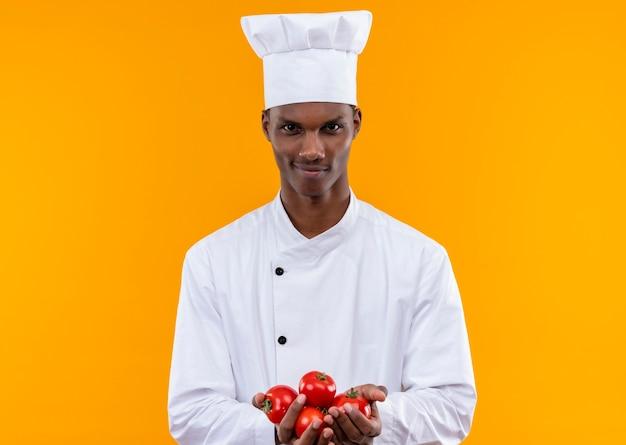シェフの制服を着た若い自信を持ってアフリカ系アメリカ人の料理人は、コピースペースでオレンジ色の背景に分離された両手でジャガイモを保持します