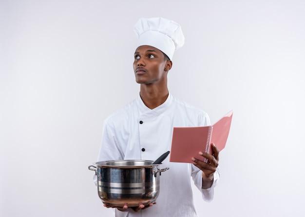 シェフの制服を着た若い自信を持ってアフリカ系アメリカ人の料理人は、コピースペースと孤立した白い背景で横に見ている鍋とノートブックを保持します
