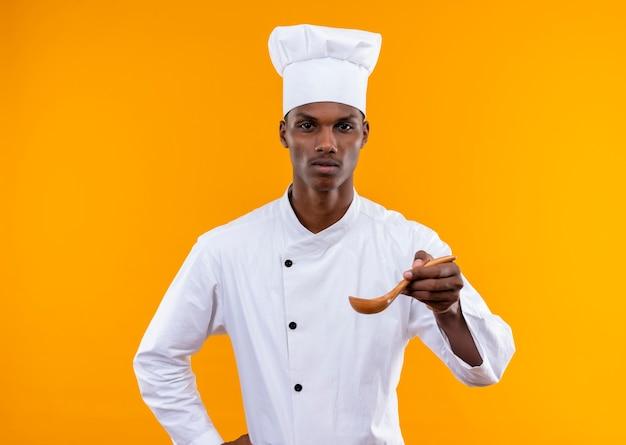 シェフの制服を着た若い自信を持ってアフリカ系アメリカ人の料理人は木のスプーンを保持し、コピースペースでオレンジ色の背景に分離された腰に手を置きます