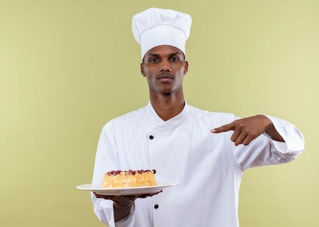 コピースペースで緑の背景に分離されたプレート上のケーキでシェフの制服のポイントで若い自信を持ってアフリカ系アメリカ人の料理人