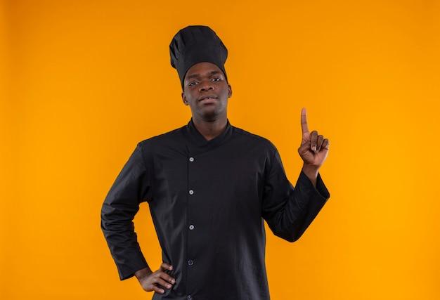 シェフの制服を着た若い自信のあるアフリカ系アメリカ人の料理人が上を向いて、コピースペースのあるオレンジ色の腰に手を置きます