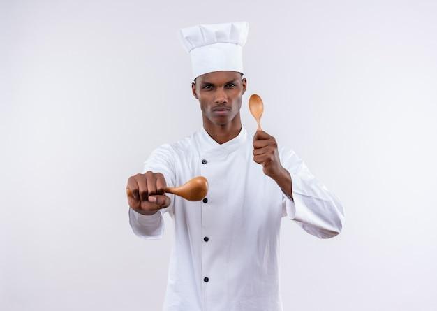 シェフの制服を着た若い自信を持ってアフリカ系アメリカ人の料理人は、コピースペースと孤立した白い背景の上の木のスプーンで守るふりをします