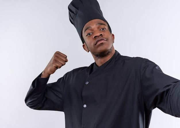 シェフの制服を着た若い自信を持ってアフリカ系アメリカ人の料理人は、カメラを保持するふりをして、コピースペースで白い背景に分離された拳を上げます