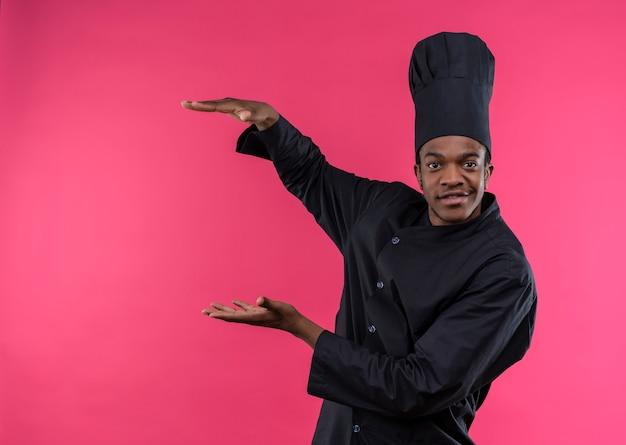 シェフの制服を着た若い自信のあるアフリカ系アメリカ人の料理人は、コピースペースでピンクの背景に孤立した何かを保持するふりをします