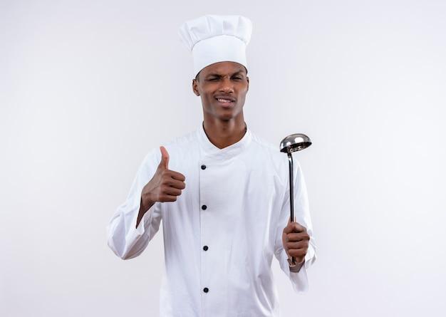 シェフの制服を着た若い自信を持ってアフリカ系アメリカ人の料理人は、目で点滅し、コピースペースで白い背景に隔離されたおたまを保持します