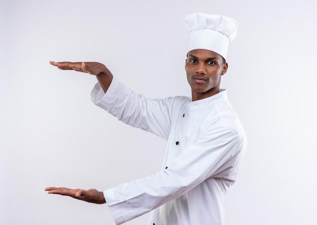 シェフの制服を着た若い自信のあるアフリカ系アメリカ人の料理人は、コピースペースで白い背景に隔離された何かを保持するふりをします
