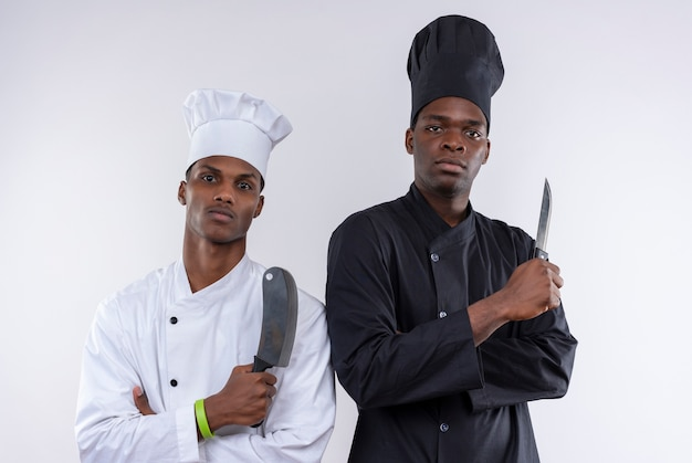 腕を組んでシェフの制服を着た若い自信を持ってアフリカ系アメリカ人の料理人は、白い背景で隔離のナイフを保持します