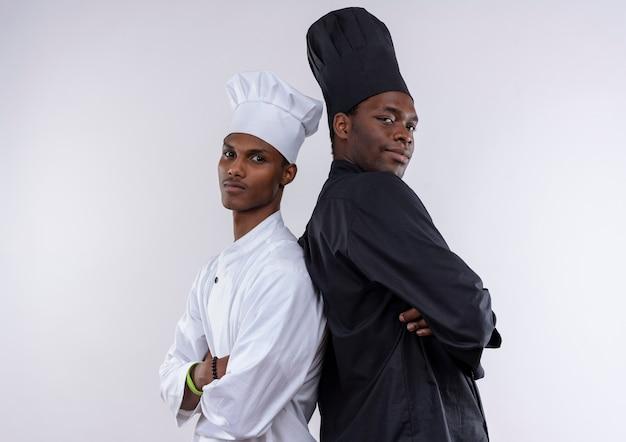 腕を組んでシェフの制服を着た若い自信を持ってアフリカ系アメリカ人の料理人は、白い背景で隔離の背中合わせに立っています