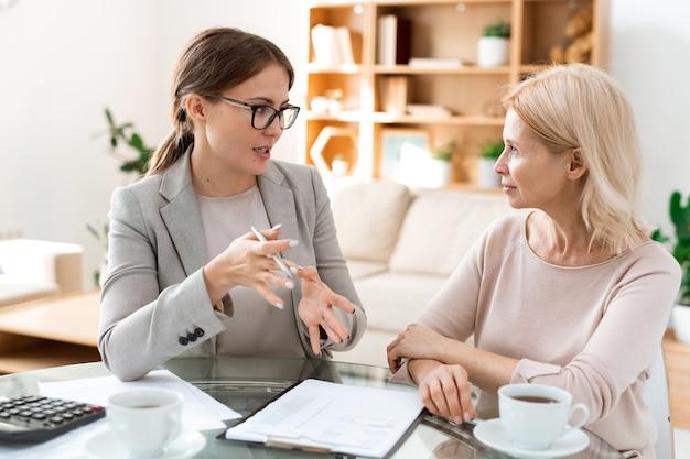 交渉中に彼女の成熟した金髪のクライアントの質問に答える正装の若い自信のあるエージェント