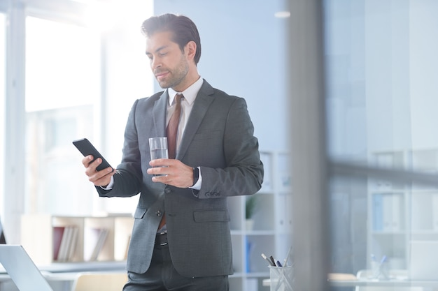 Young confident agent with glass of water scrolling in smartphone while going to make call