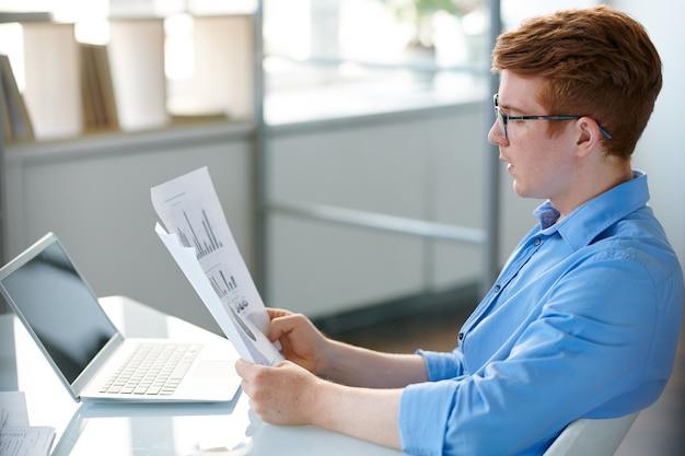 チャートとグラフで財務書類を見て自信を持って若いアナリスト