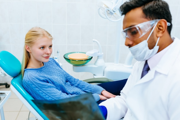 Young confident asian male dentist checking teeth x ray of patient. dental clinic concept.