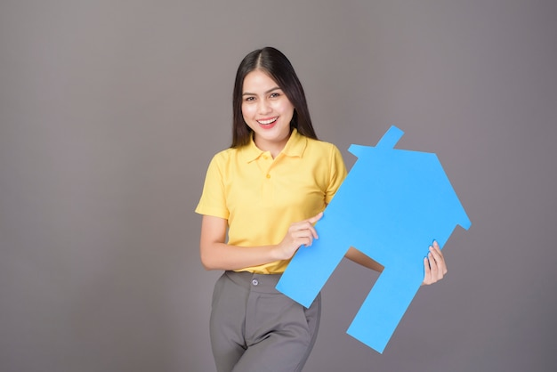 Young confident beautiful woman wearing yellow shirt is holding a home singn on grey