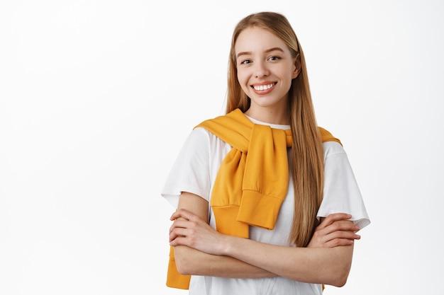Giovane ragazza bionda sicura di sé con lunghi capelli naturali, braccia incrociate sul petto e sorridente determinata, in piedi come una professionista, in piedi su un muro bianco