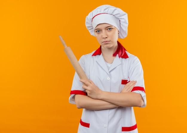 Il giovane chef femminile biondo sicuro in uniforme del cuoco unico attraversa le braccia e tiene il mattarello isolato sulla parete arancione