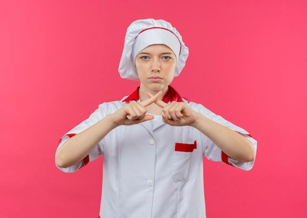 Il giovane chef femminile biondo fiducioso in uniforme del cuoco unico incrocia i gesti delle dita non isolati sulla parete rosa