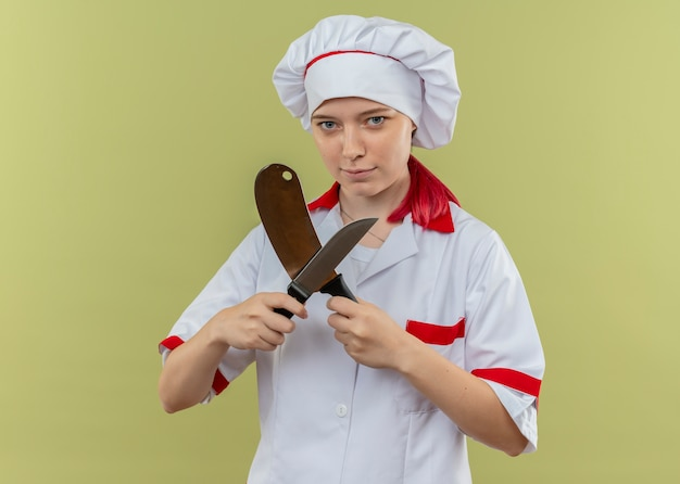 Young confident blonde female chef in chef uniform crosses knifes and looks isolated on green wall