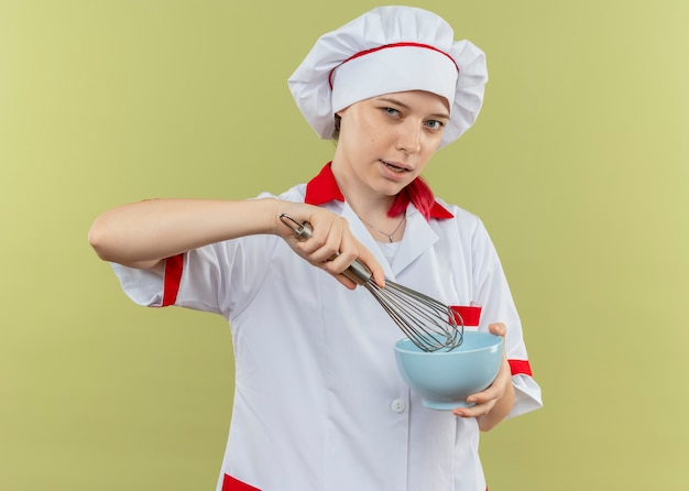 Young confident blonde female chef in chef uniform holds bowl and whisk isolated on green wall