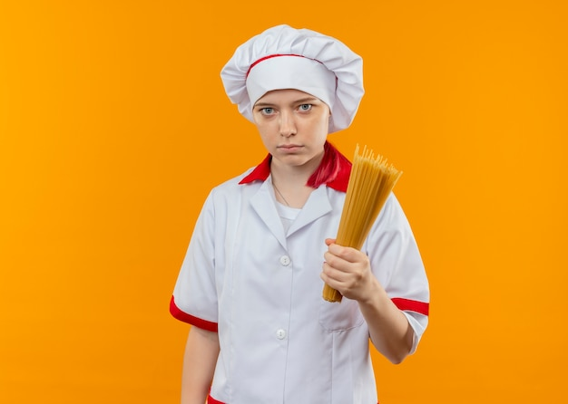 Il giovane chef femminile biondo sicuro in uniforme del cuoco unico tiene il mazzo di spaghetti isolato sulla parete arancione