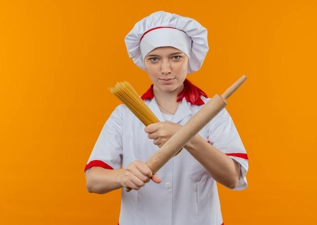 Il giovane chef femminile biondo sicuro in uniforme del cuoco unico tiene e attraversa il mazzo di spaghetti e mattarello isolato sulla parete arancione
