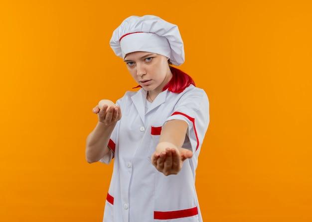 Il giovane cuoco unico femminile biondo sicuro in uniforme del cuoco unico tiene fuori l'uovo isolato sulla parete arancione