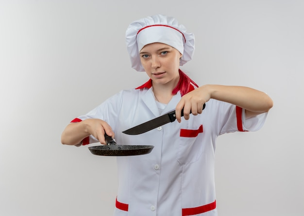 Young confident blonde female chef in chef uniform holds frying pan and knife isolated on white wall