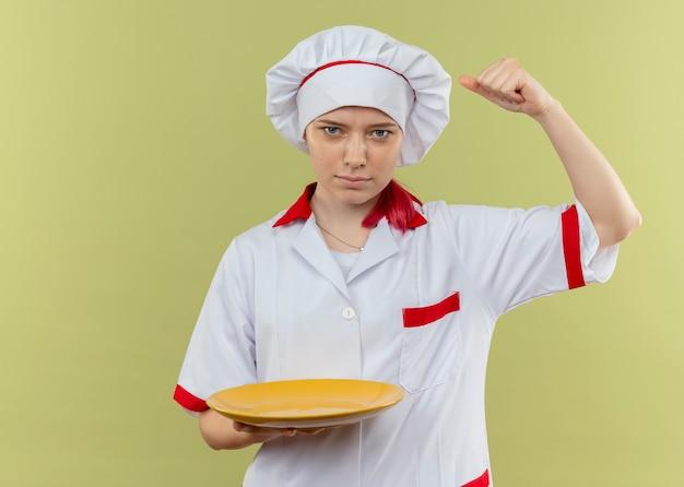 Il giovane chef femminile biondo fiducioso in uniforme da chef tiene il piatto e solleva il pugno isolato sulla parete verde