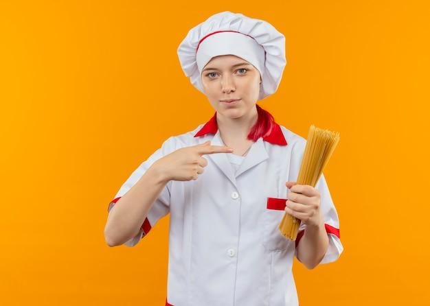 Il giovane chef femminile biondo fiducioso in uniforme del cuoco unico tiene e indica il mazzo di spaghetti isolato sulla parete arancione