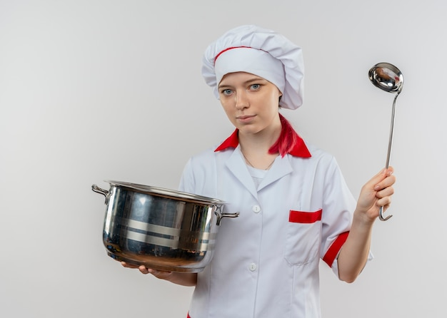 Young confident blonde female chef in chef uniform holds pot and ladle isolated on white wall