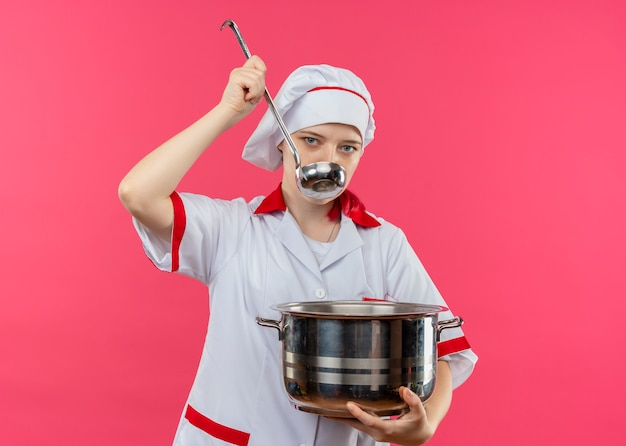Young confident blonde female chef in chef uniform holds pot and pretends to try with ladle isolated on pink wall