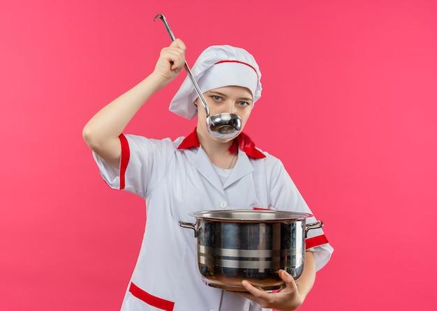 Il giovane chef femmina bionda fiducioso in uniforme da chef tiene la pentola e finge di provare con il mestolo isolato sulla parete rosa