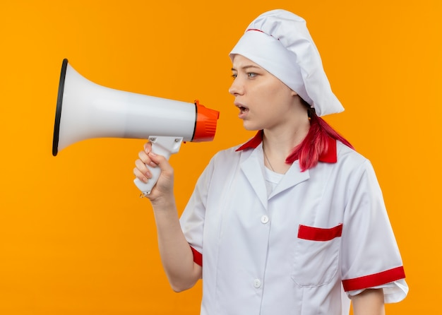 Young confident blonde female chef in chef uniform shouts through loud speaker and looks at side isolated on orange wall