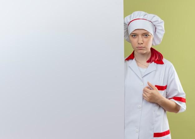 Il giovane chef femmina bionda fiducioso in uniforme da chef sta dietro il muro bianco e sembra isolato sulla parete verde