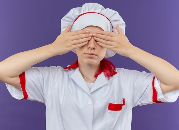シェフの制服を着た若い自信を持って金髪の女性シェフは、紫色の壁に隔離された手で目を閉じます