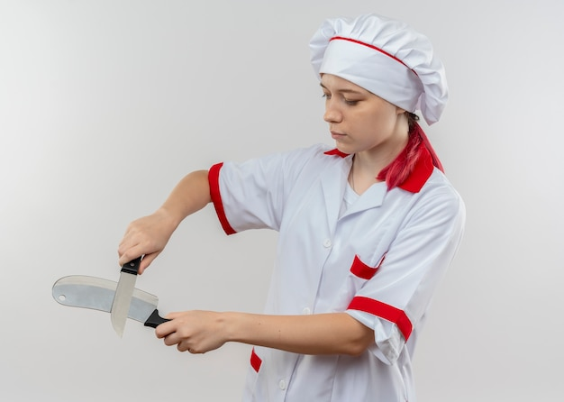 シェフの制服を着た若い自信を持って金髪の女性シェフが交差し、白い壁に分離されたナイフを見る